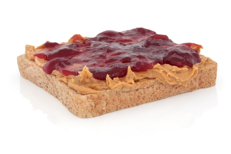 Peanut butter and raspberry jam on brown wholemeal bread, over white background. photo