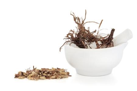 valerian: Valerian root di erba in un mortaio di porcellana con pestello con un mucchio di trito di lato, isolato su sfondo bianco. Valeriana. Giorno moderno equivalente � valium e diazipam.