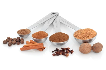 Spice selection of nutmeg, clove, cinnamon and allspice in powder form in stainless steel measuring spoons with corresponding whole spices over white background. Right to left. photo