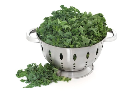 Kale green cabbage in a stainless steel colander and loose, over white background. photo