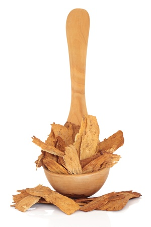 qui: Astragalus root in an olive wood ladle and scattered, isolated over white background. Used extensively in chinese herbal medicine to speed healing and treat diabetes. Zhi huang qui. Astragali radix. Stock Photo