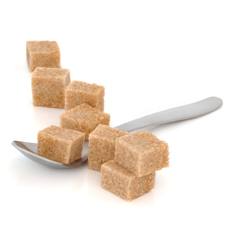 sugar cubes: Brown sugar cubes in a spoon and scattered over white background. Selective focus.