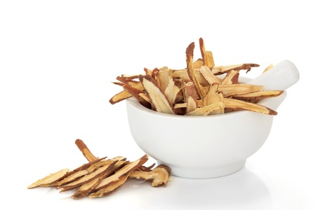 Licorice root in a porcelain mortar with pestle. Used in traditional chinese herbal medicine and for culinary purposes, isolated over white background. photo