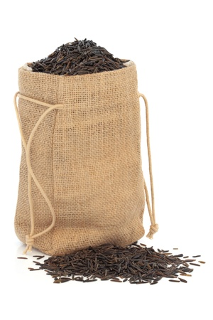 Wild rice in a hessian sack and scattered, isolated over white background. photo