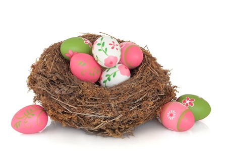 Easter egg clutch in a natural bird nest and loose, over white background. Banque d'images - 8765819