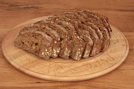 bread soda: Soda bread loaf in slices on a carved wooden beech bread board over oak wood. Stock Photo