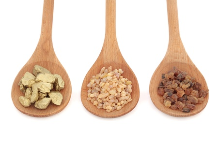 Gold, frankincense and myrrh in wooden spoons, over white background. Selective focus.