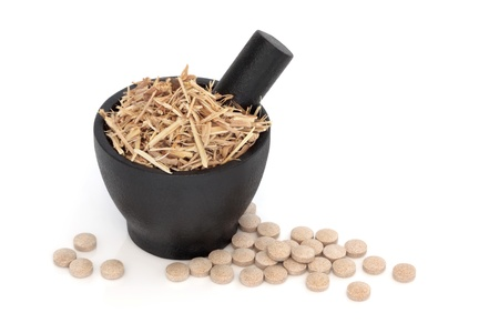 Ginseng in a black granite mortar with pestle and scattered vitamin pills, over white background.