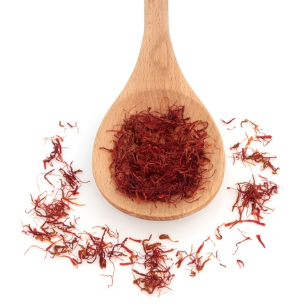 Saffron spice in a wooden spoon and scattered , over white background. photo