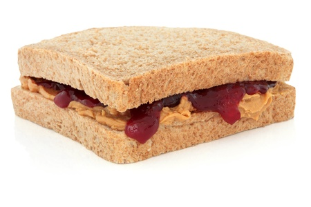 Peanut butter and raspberry jam sandwich on brown bread, over white background. photo