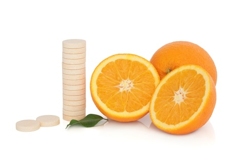 Vitamin c tablet stack with orange fruit whole and in half with leaf sprig, over white background. photo