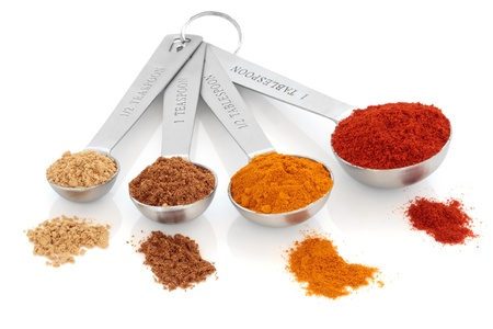 Spice selection of paprika, turmeric, chinese five spice and ginger in stainless steel measuring spoons, and loose, over white background. Right to left. Selective focus. Stock fotó