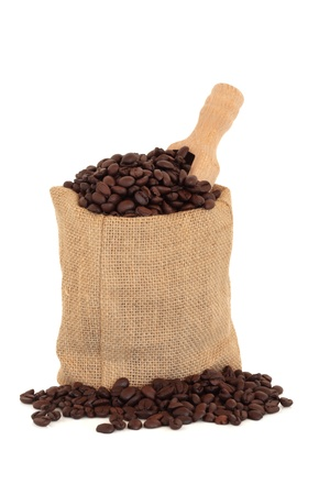 hessian bag: Coffee beans in a hessian bag with a wooden scoop and scattered, over white background.