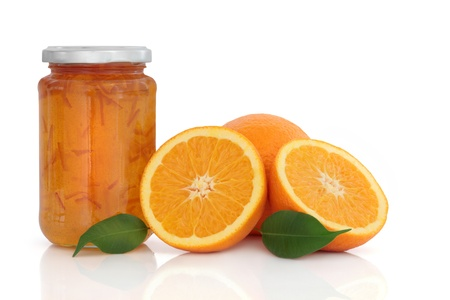 jam: Marmalade jam in a jar with orange fruit whole and in halves with leaf sprigs, over white background. Stock Photo