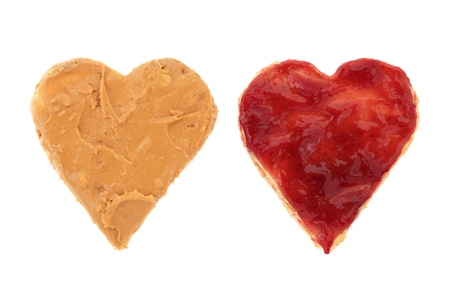 raspberry jelly: Peanut butter and raspberry jam on brown heart shaped wholemeal bread, over white background.