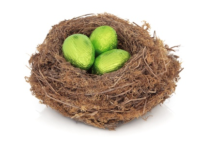 Chocolate easter eggs in a natural bird nest wrapped in green foil, over white background.  photo