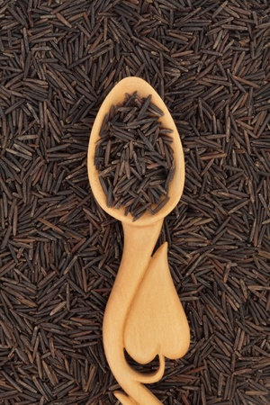 Wild rice in a carved wooden spoon with heart shape and forming a background. Stock Photo - 9026361