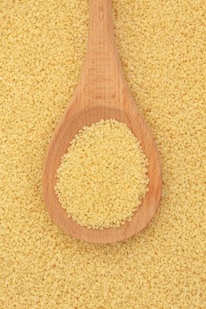 Couscous in a wooden spoon and forming a background. photo
