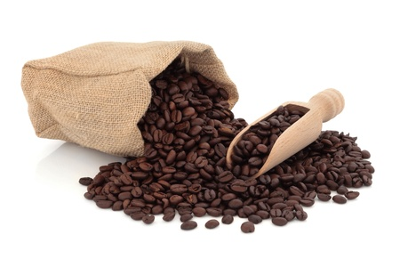 beverage in bean:  Coffee beans in a wooden scoop and spilling out from a hessian bag, over white background. Stock Photo