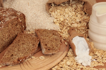 bi: Soda bread in slices with wholemeal flour, oat flakes, bi carbonate of soda, and buttermilk in a jug.