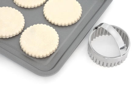Pastry biscuit dough on a baking tray with cookie cutter, over white background. photo