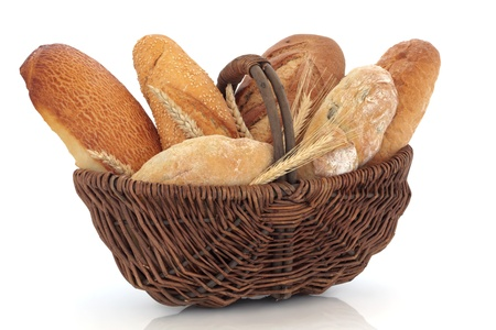 Bread loaf selection of tiger, sesame, rye, olive and french navette, with ears of wheat and corn in an old wicker basket, over white background. photo