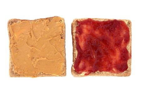 peanut butter and jelly:  Peanut butter and raspberry jam open sandwich on sliced brown bread, over white background.