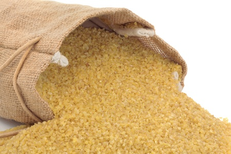 hessian: Bulgur wheat spilling out from a hessian sack, over white background.