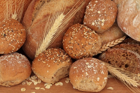 Bread loaf rustic selection of olive, rye ,soda, tiger bloomer breads, with brown granary and oated rolls and ears of wheat. photo