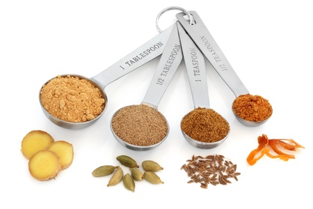 Spice selection of ginger, cardamom, cumin and mace in ground form in stainless steel measuring spoons with corresponding whole spices over white background.  Left to right. Selective focus. photo