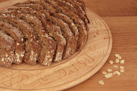 bread soda: Soda bread loaf in slices on a carved wooden bread board with loose oat flakes.