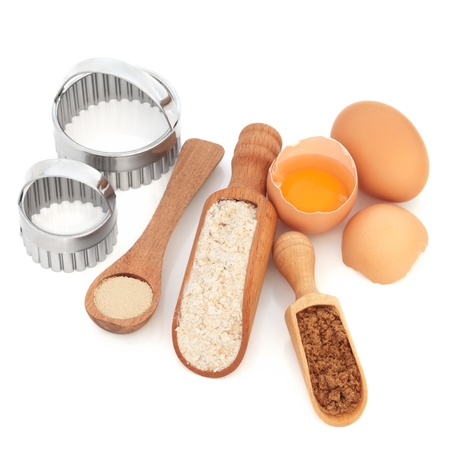 Baking products and equipment, with wholegrain flour, yeast,sugar and eggs, with wooden spoon, scoop,  and metal cookie cutters, over white background. photo