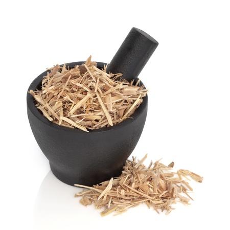 mortero: Ginseng en un granito negro de mortero con mortero y dispersos, sobre fondo blanco.