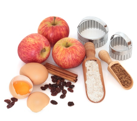 Apple pie ingredients including royal gala apples, sultanas, cinnamon, wholegrain flour, eggs and sugar with wooden scoops and cutters over white background. photo