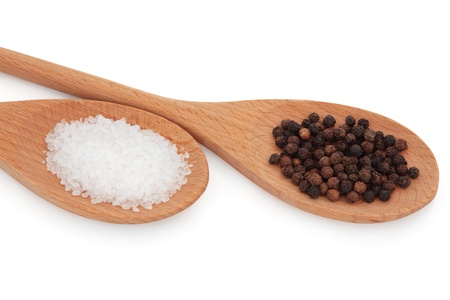 Sea salt and black peppercorns in two wooden spoons, over white background. photo