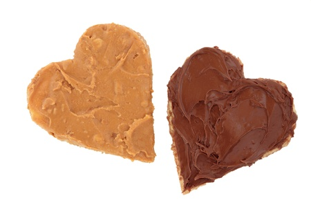 Peanut butter and chocolate spread on brown heart shaped wholemeal bread, over white background. photo