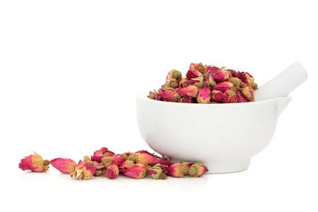 Rose flower buds in a porcelain mortar with pestle and scattered isolated over white background. Used in rose oil and alternative flower remedies.  Rosa damascena photo
