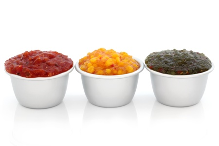 gherkin:  Burger relish selection of red tomato, sweetcorn and green gherkin  in metal serving dishes, over white background. Stock Photo
