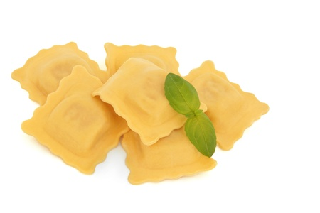 Ravioli pasta stack with basil herb leaf sprig isolated over white background. Selective focus