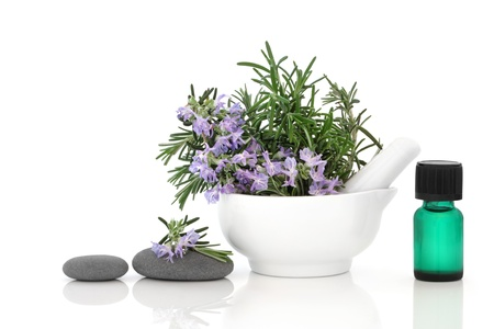 mortar and pestle:   Rosemary herb flower sprigs in a porcelain mortar with pestle, spa stones, and aromatherapy essential oil bottle, isolated over white background.
