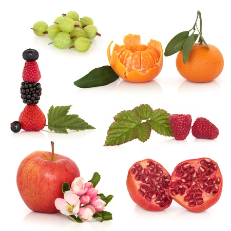 Fruit selection of gooseberry, tangerine, apple, pomegranate, raspberry, blackberry, strawberry, blueberry and blackcurrant, with leaf sprigs and flower blossom, isolated over white background. photo