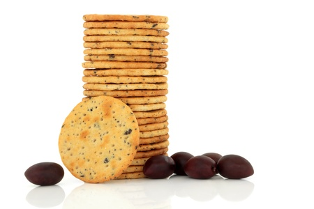 kalamata: Olive cracker biscuit stack with fresh black kalamata olives isolated over white background.