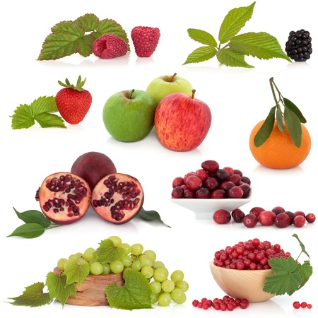 Fruit selection of raspberry, strawberry, blackberry, pomegranate, apple, tangerine, cranberry, grape and redcurrant, with leaf sprigs, isolated over white background. photo