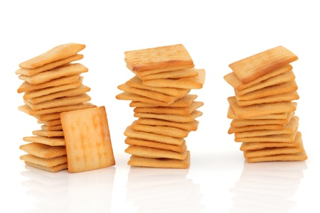 Cheese salted cracker biscuits in three stacks, also known as cheeselets, isolated over white background. photo
