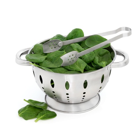 a colander: Spinach leaves in a stainless steel colander with metal tongs isolated over white background.