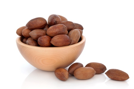 pecan: Pecan nuts in a beech wood bowl and loose isolated over white background.