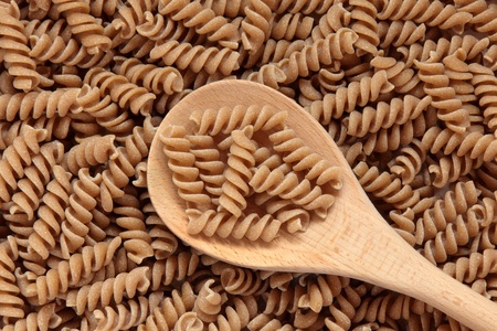 durham: Fusilli pasta made with durham wheat in a wooden spoon and forming a background.