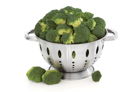 a colander: Broccoli vegetable in a stainless steel colander and loose, isolated over white background.