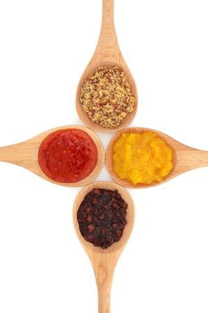 wholegrain mustard: Piccalilli, sweet vegetable relish,  chili sauce, and wholegrain mustard in wooden spoons isolated over white background. Stock Photo