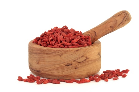 goji: Goji berries in an olive wood mortar with pestle isolated over white background. Stock Photo